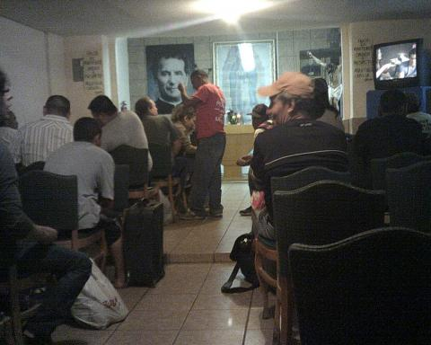 back of room full of people watching TV
