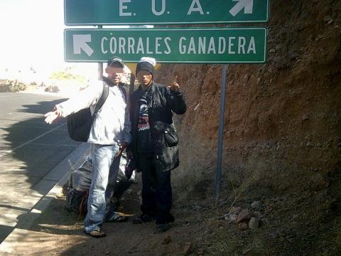 men in front of sign to US border