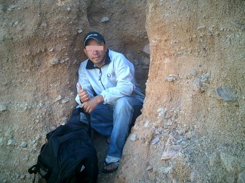 man in hole in desert canyon wall