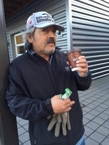 man standing outside with coffee cup