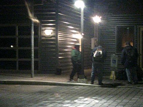 people standing in dark on a street corner