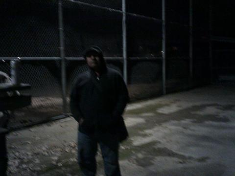 man standing in front of chain link fence dark