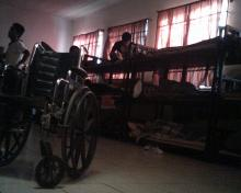 sleeping area with wheelchair in foreground