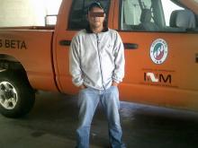 man posing in front of orange truck