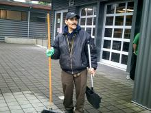 man with broom and dustpan on street